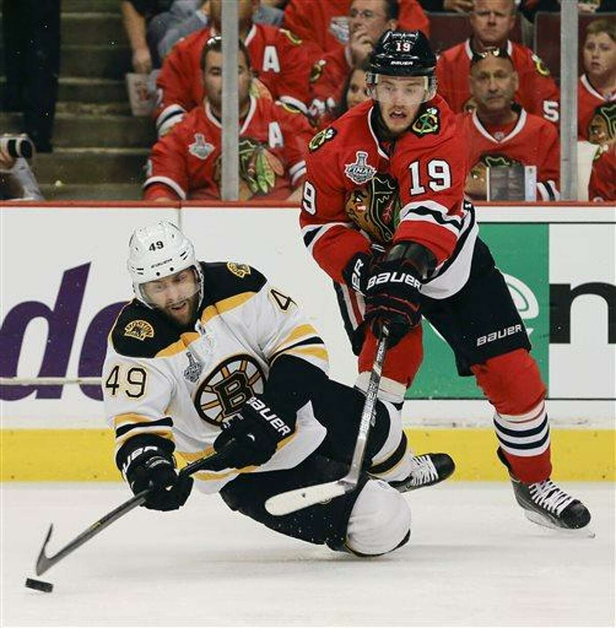 Boston Bruins center Rich Peverley (49) falls to the ice as he keeps the puck from Chicago Blackhawks center Jonathan Toews (19) in the second period during Game 2 of the NHL hockey Stanley Cup Finals, Saturday, June 15, 2013, in Chicago. (AP Photo/Nam Y. Huh)
