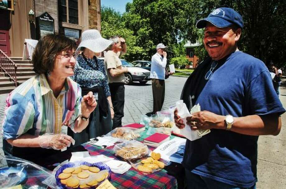 Melanie Stengel/New Haven Register    Deborah Johnson (L), of Hamden, helps Jose Luis, of New Haven, fill a bag of Cookies from the table in front of Trinity Episcopal Church. Proceeds from donations for the cookies will go to Columbus House.