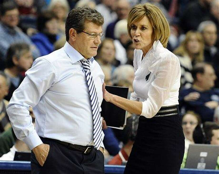 Connecticut coach Geno Auriemma, left, is pushed back off the court by associate head coach Chris Dailey during the second half of an NCAA college basketball game against Duke in Storrs, Conn., Monday, Jan. 21, 2013. Connecticut won 79-49. (AP Photo/Jessica Hill) Photo: AP / FR125654 AP