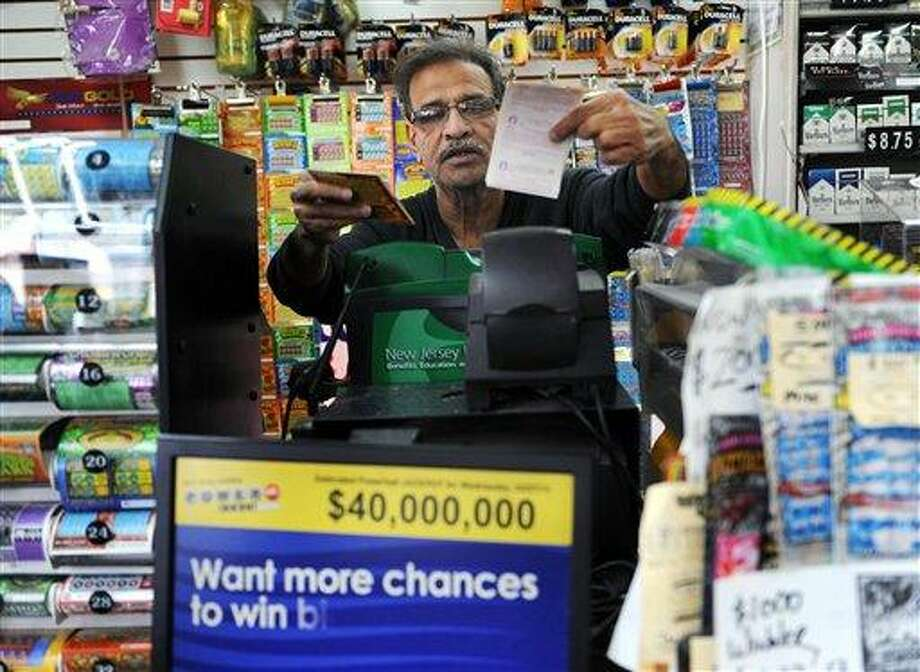 Baiju Amin hands lottery tickets to a customer at Union Food Store in Totowa, N.J. on Sunday, March 24, 2013. The lone winning ticket for a $338.3 million Powerball drawing was sold in New Jersey. Details on where and when the winning ticket was purchased and other related information were not disclosed Sunday by New Jersey Lottery officials, who also would not say if anyone claiming to hold the ticket had contacted them as of Sunday afternoon. (AP Photo/The Record (Bergen County NJ), Tyson Trish) Photo: AP / The Record of Bergen County