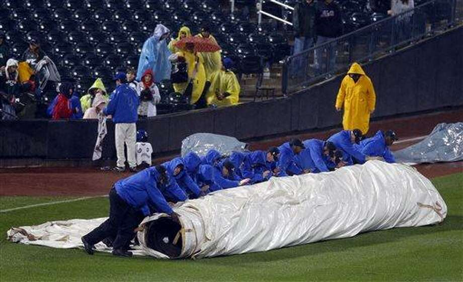 The Citi Field grounds crew rolls out the tarp to cover the field in a heavy rain before the ninth inning with the score tied at 5-5 in a baseball game between the Atlanta Braves and the New York Mets at Citi Field in New York, Friday, May 24, 3013. (AP Photo/Paul J. Bereswill) Photo: AP / FR168017 AP