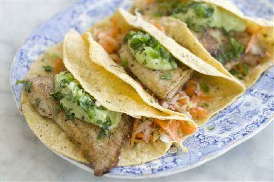 This June 3, 2013 photo taken in Concord, N.H. shows a recipe for healthy fish tacos with avocado. (AP Photo/Matthew Mead) Photo: AP / FR170582 AP