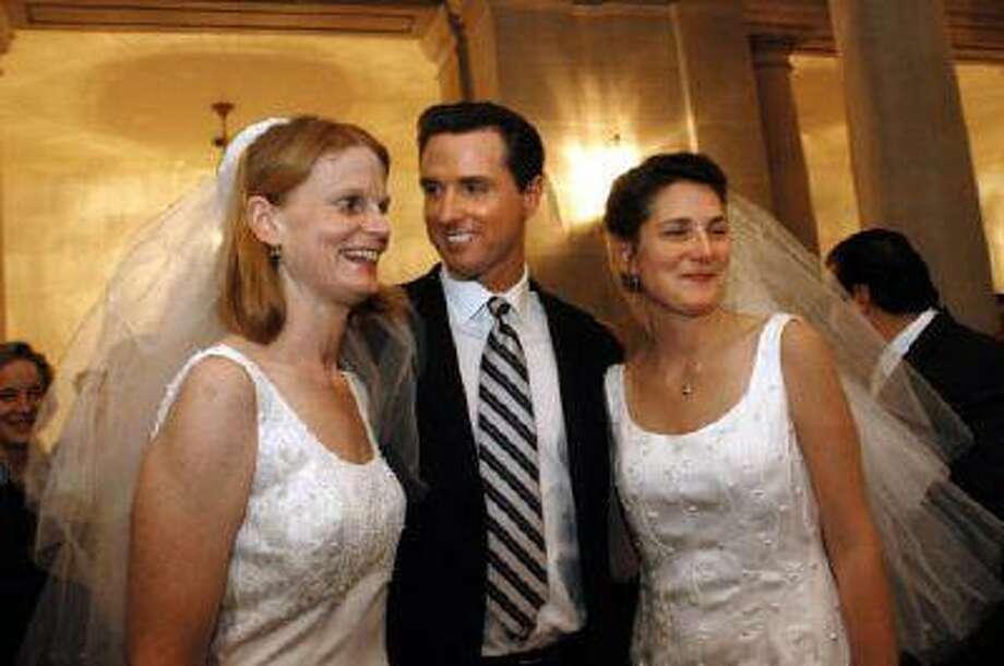 San Francisco Mayor Gavin Newsom stands between newlyweds Cissie Bonini, left, and Lora Pertle at San Francisco City Hall on Feb. 13, 2004. Photo: AP / AP