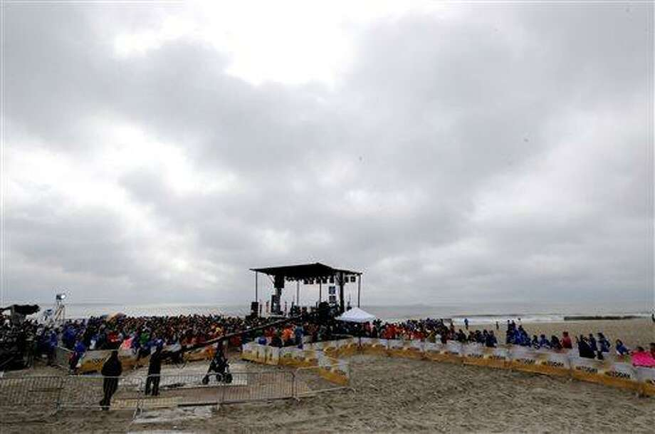 People gather around a stage as musical group Fun performs on the beach, Friday, May 24, 2013, in Seaside Heights, N.J. New Jersey Gov. Chris Christie cut a ribbon to symbolically reopen the state's shore for the summer season, seven months after being devastated by Superstorm Sandy. Several beach communities have annual beach ribbon cuttings, announcing they are back in business. But this year's ceremonies are more poignant seven months after a storm that did an estimated $37 billion of damage in the state. (AP Photo/Julio Cortez) Photo: AP / AP