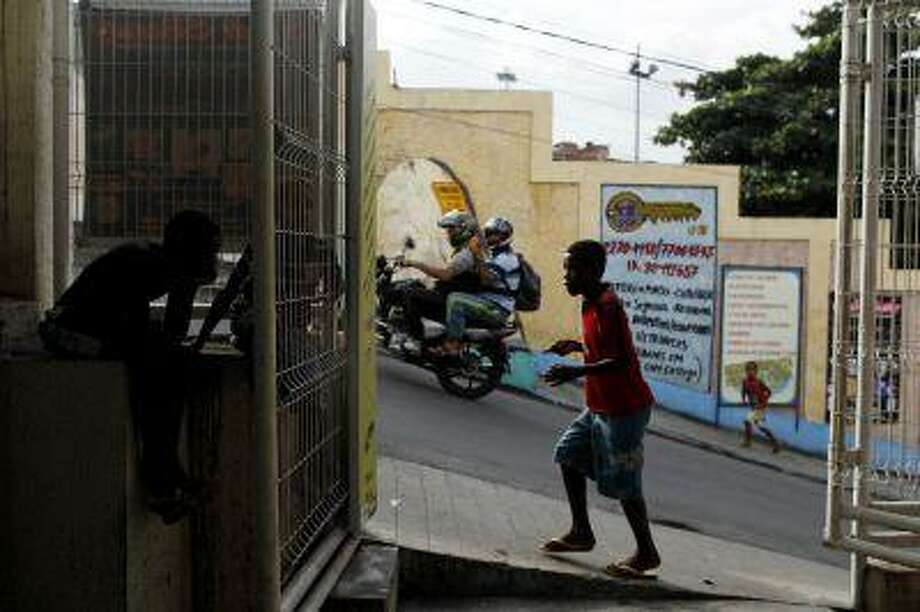 People walk past closed shops at the Complexo do Alemao slum in Rio de Janeiro May 23, 2013. Photo: REUTERS / X00856