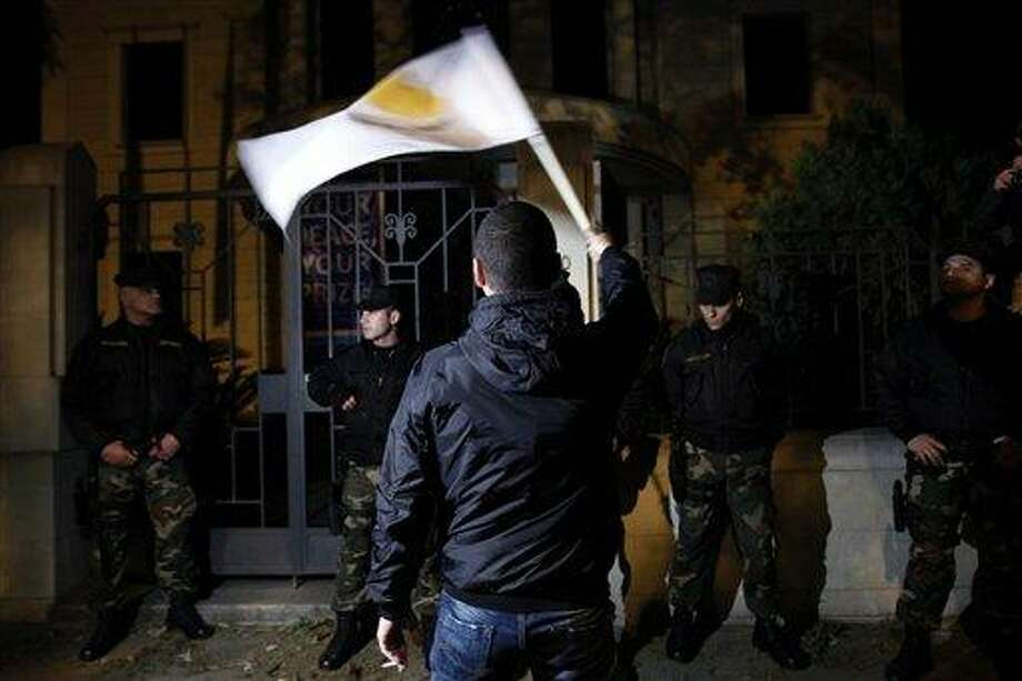 A protestor waves a Cyprus flag in front of riot policemen during an anti-bailout rally outside of European Union house in Nicosia, Cyprus, Sunday, March 24, 2013. After failing for a week to find a solution to a crisis that could force their country into bankruptcy, Cypriot politicians turned to the European Union on Sunday in a last-ditch effort to help the island nation forge a viable plan to secure an international bailout. (AP Photo/Petros Karadjias) Photo: AP / AP