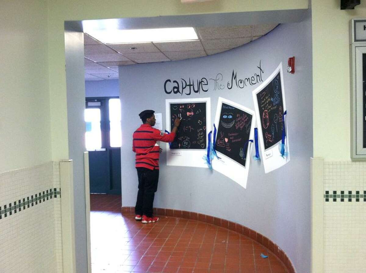 """Contributed photo: A student adds another piece to the """"Capture the Moment"""" exhibit at High School in the Community."""