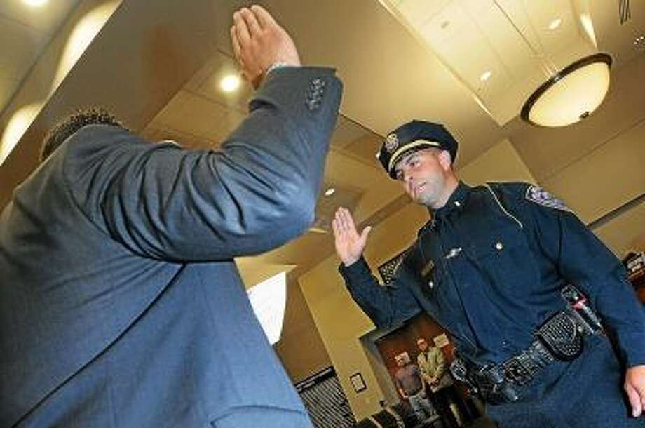 Catherine Avalone/The Middletown Press Middletown Police Officer Michael Desena, 37 is sworn in at the rank of lieutenant Friday afternoon by Mayor Dan Drew in the council chambers at Middletown City Hall and will be working the midnight patrol shift commander. / TheMiddletownPress