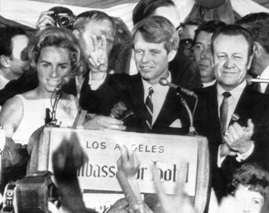 U.S. Sen. Robert F. Kennedy holds two fingers up in a victory sign as he talks to campaign workers at the Ambassador Hotel in Los Angeles, Ca., June 5, 1968.  He is flanked by his wife Ethel, left, and his California campaign manager, Jesse Unruh, speaker of the California Assembly. After making the speech, Kennedy left the platform and was assassinated in an adjacent room.  (AP Photo) Photo: AP / 1968 AP
