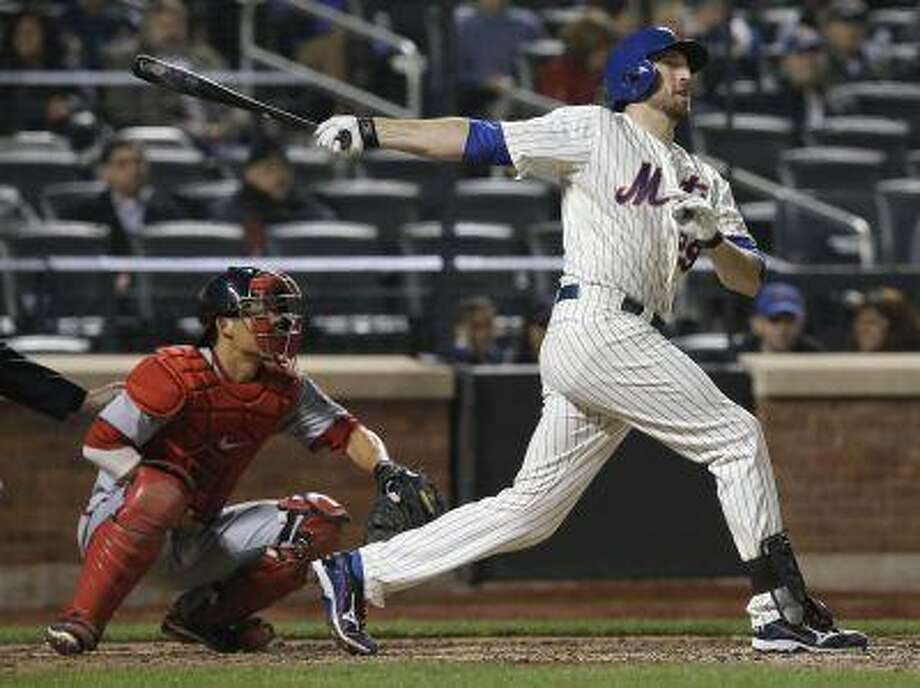 New York Mets batter Ike Davis hits a two-run home run, his second home run of the game, in front of Washington Nationals catcher Kurt Suzuki (L) during the eighth inning of their MLB National League game at CitiField in New York, April 19, 2013. REUTERS/Ray Stubblebine (UNITED STATES - Tags: SPORT BASEBALL) Photo: REUTERS / X00272