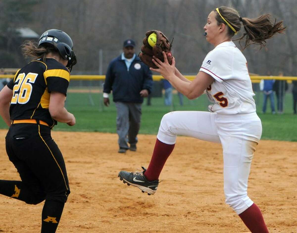 Teresa Marchitto of Amity left, is tagged out at first base by Maddie Mizenko of Sheehan during the fifth inning on Friday in Woodbridge. Amity won 7-1. Photo by Peter Hvizdak/New Haven Register