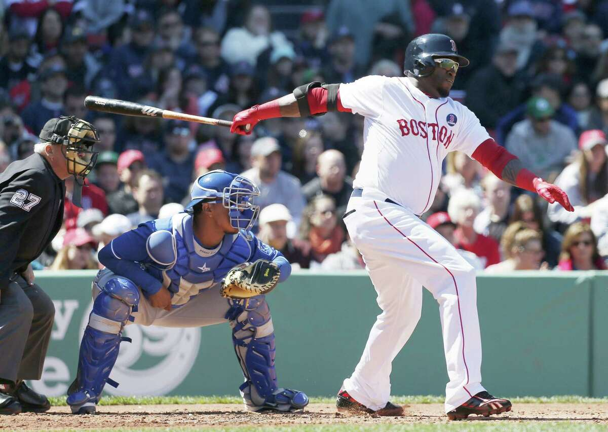 CORRECTS TO APRIL 21 NOT 20 - Boston Red Sox's David Ortiz, right, follows through on an RBI-single in front of Kansas City Royals catcher Salvador Perez, center, in the first inning of the first game of a baseball doubleheader in Boston, Sunday, April 21, 2013. (AP Photo/Michael Dwyer)