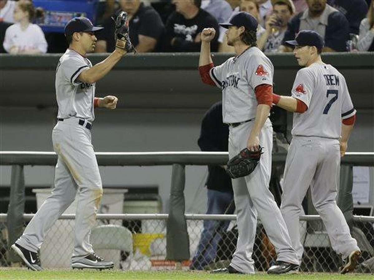 Boston Red Sox center fielder Jacoby Ellsbury, left, celebrates with starter Clay Buchholz, center, and shortstop Stephen Drew after catching a fly ball hit by Chicago White Sox's Alexei Ramirez during the fifth inning of a baseball game in Chicago, Wednesday, May 22, 2013. (AP Photo/Nam Y. Huh)