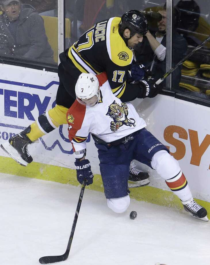 Boston Bruins left wing Milan Lucic, top, and Florida Panthers defenseman Dmitry Kulikov  keep their eyes on the puck as they slam into the boards in the first period of an NHL hockey game at the TD Garden, in Boston Sunday, April 21, 2013. (AP Photo/Steven Senne) Photo: AP / AP