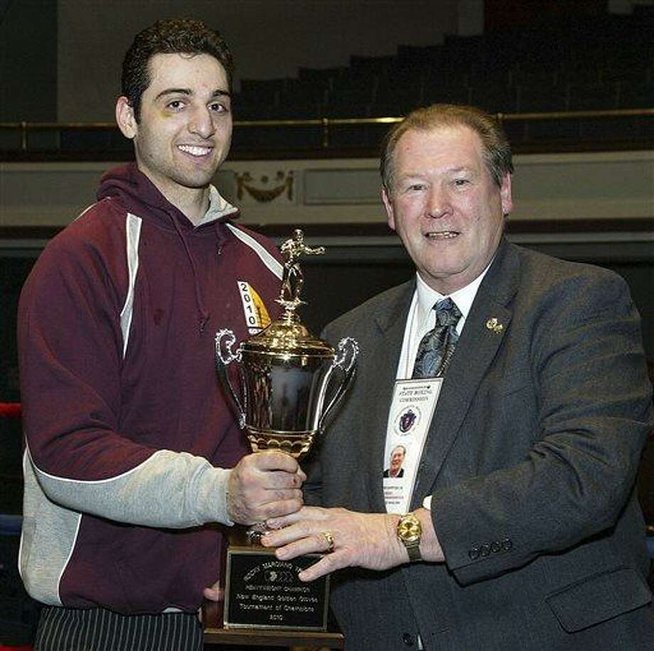 In this Feb. 17, 2010, photo, Tamerlan Tsarnaev, left, accepts the trophy for winning the 2010 New England Golden Gloves Championship from Dr. Joseph Downes, right, in Lowell, Mass. Tsarnaev, 26, who had been known to the FBI as Suspect No. 1 in the Boston Marathon Explosions and was seen in surveillance footage in a black baseball cap, was killed overnight on Friday, April 19, 2013, officials said. (AP Photo/The Lowell Sun, Julia Malakie) Photo: ASSOCIATED PRESS / THE LOWELL SUN PUBLISHING CO2010
