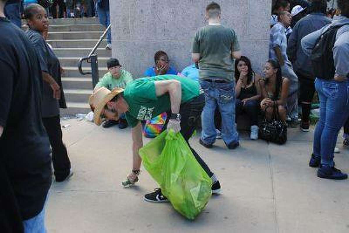 Dwaine Witt, a multiple sclerosis patient, picks up trash at a recent event. Some medical-marijuana dispensaries have donated their time for charitable causes. (Photo via Green Team)