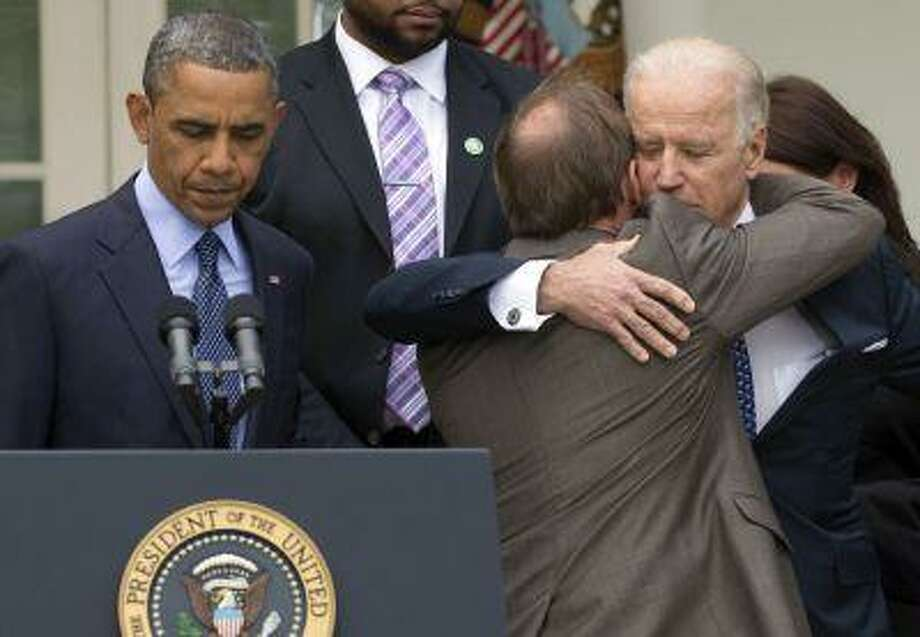 President Barack Obama stands at the podium at left as Mark Barden, the father of Newtown shooting victim Daniel is embraced by Vice President Joe Biden during a news conference in the Rose Garden of the White House, Wednesday, April 17, 2013, in Washington, about measures to reduce gun violence. (AP Photo/Carolyn Kaster) Photo: AP / AP