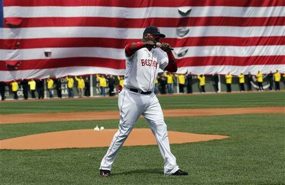 Boston Red Sox's David Ortiz pumps his fist in front of an Amarican flag and a line of Boston Marathon volunteers, background, after addressing the crowd before a baseball game between the Boston Red Sox and the Kansas City Royals in Boston, Saturday, April 20, 2013. (AP Photo/Michael Dwyer) Photo: AP / AP