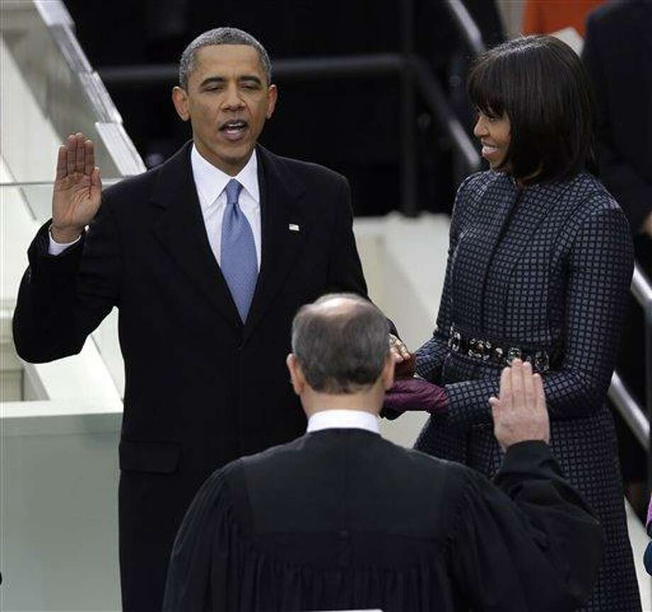 President Barack Obama receives the oath of office from Chief Justice John Roberts as first Lady Michelle holds the bible at the ceremonial swearing-in at the U.S. Capitol during the 57th Presidential Inauguration in Washington, Monday, Jan. 21, 2013. (AP Photo/Evan Vucci) Photo: AP / AP