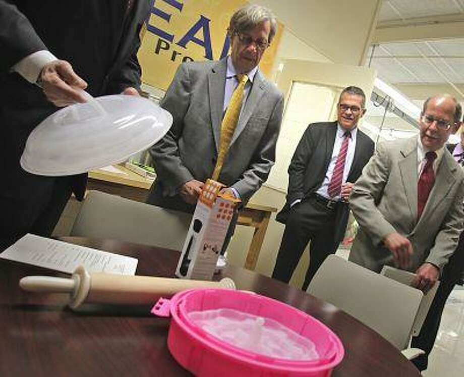 Shoals Entreprenurial Center director Giles McDaniel shows some locally designed kitchenware and tools to state and federal affiliates of the Appalachian Regional Commission, Earl Gohl, Jimmy Lester and Guy Paul Land, as they tour the Shoals Culinary Center in Florence, Ala. on Tuesday, May 14, 2013. (AP Photo/TimesDaily, Jim Hannon) Photo: AP / The TimesDaily