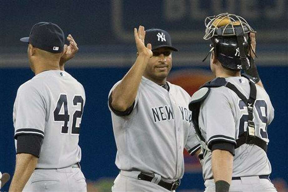 New York Yankees' Vernon Wells, center, celebrates with teammates Mariano Rivera, left, and Francisco Cerveili after defeating the Toronto Blue Jays 5-3 in a baseball game in Toronto, Saturday, April 20, 2013. (AP Photo/The Canadian Press, Chris Young) Photo: ASSOCIATED PRESS / AP2013