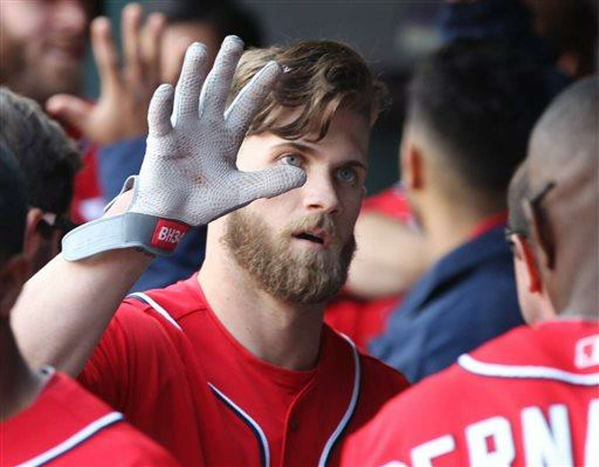 Washington Nationals' Bryce Harper celebrates with teammates after hitting a two-run home run in the third inning of a baseball game against the New York Mets in New York on Saturday, April 20, 2013. (AP Photo/Peter Morgan)