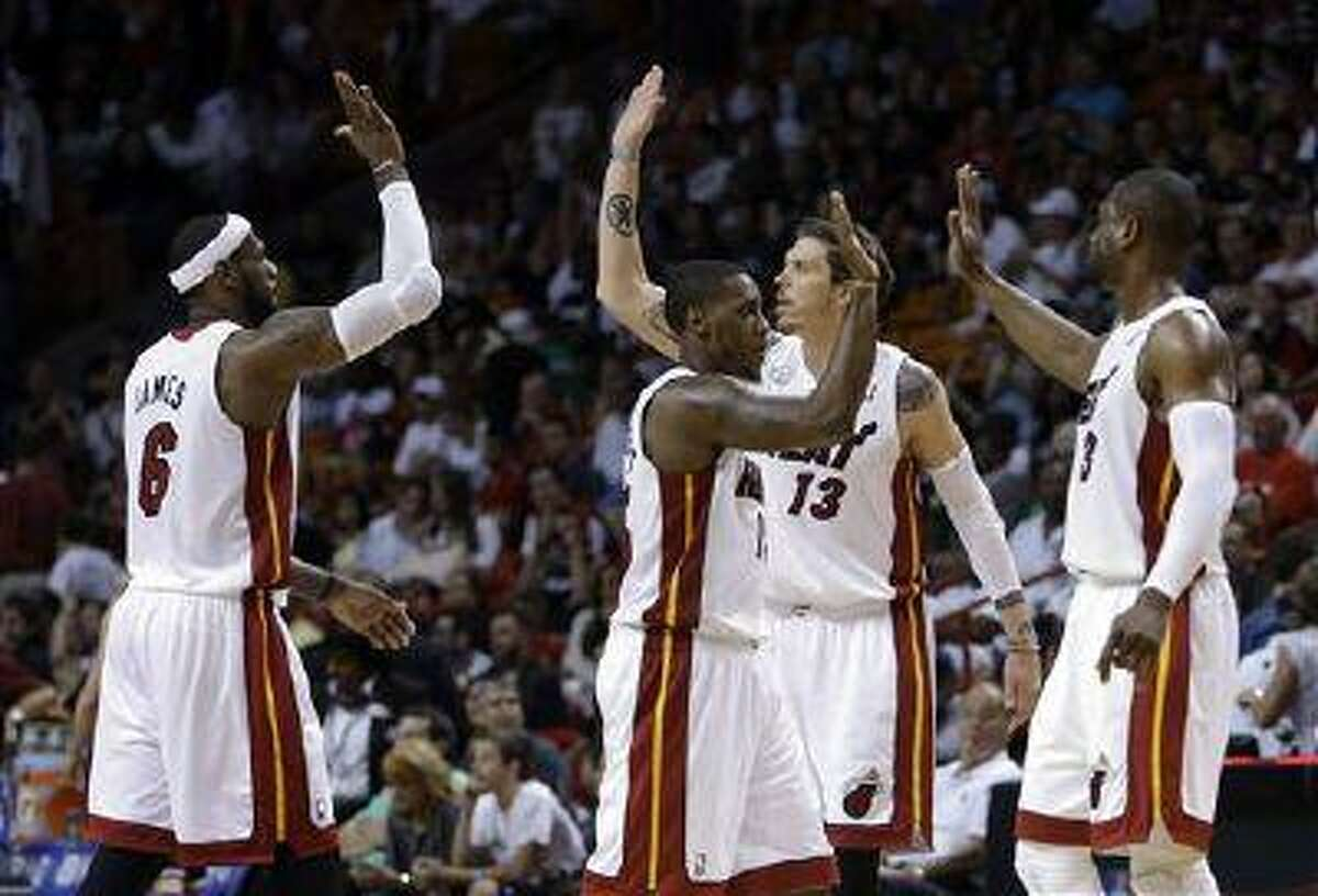 Miami Heat's LeBron James (6), Mike Miller (13), Mario Chalmers, center, and Dwyane Wade (3) high-five after during a game against the Chicago Bulls, April 14, 2013, in Miami.