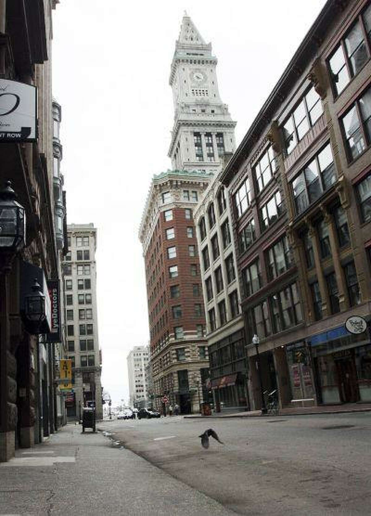 A pigeon flies along deserted State Street, as the Custom House hotel towers in the background in downtown Boston Friday, April 19, 2013. Mass transit was suspended while a suspect was hunted following bombings near the finish line of the Boston Marathon Monday. (AP Photo/Bill Sikes)
