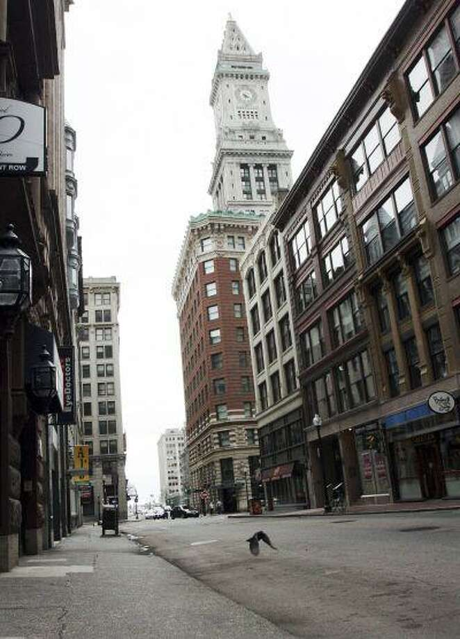 A pigeon flies along deserted State Street, as the Custom House hotel towers in the background in downtown Boston Friday, April 19, 2013. Mass transit was suspended while a suspect was hunted following bombings near the finish line of the Boston Marathon Monday. (AP Photo/Bill Sikes) Photo: AP / AP