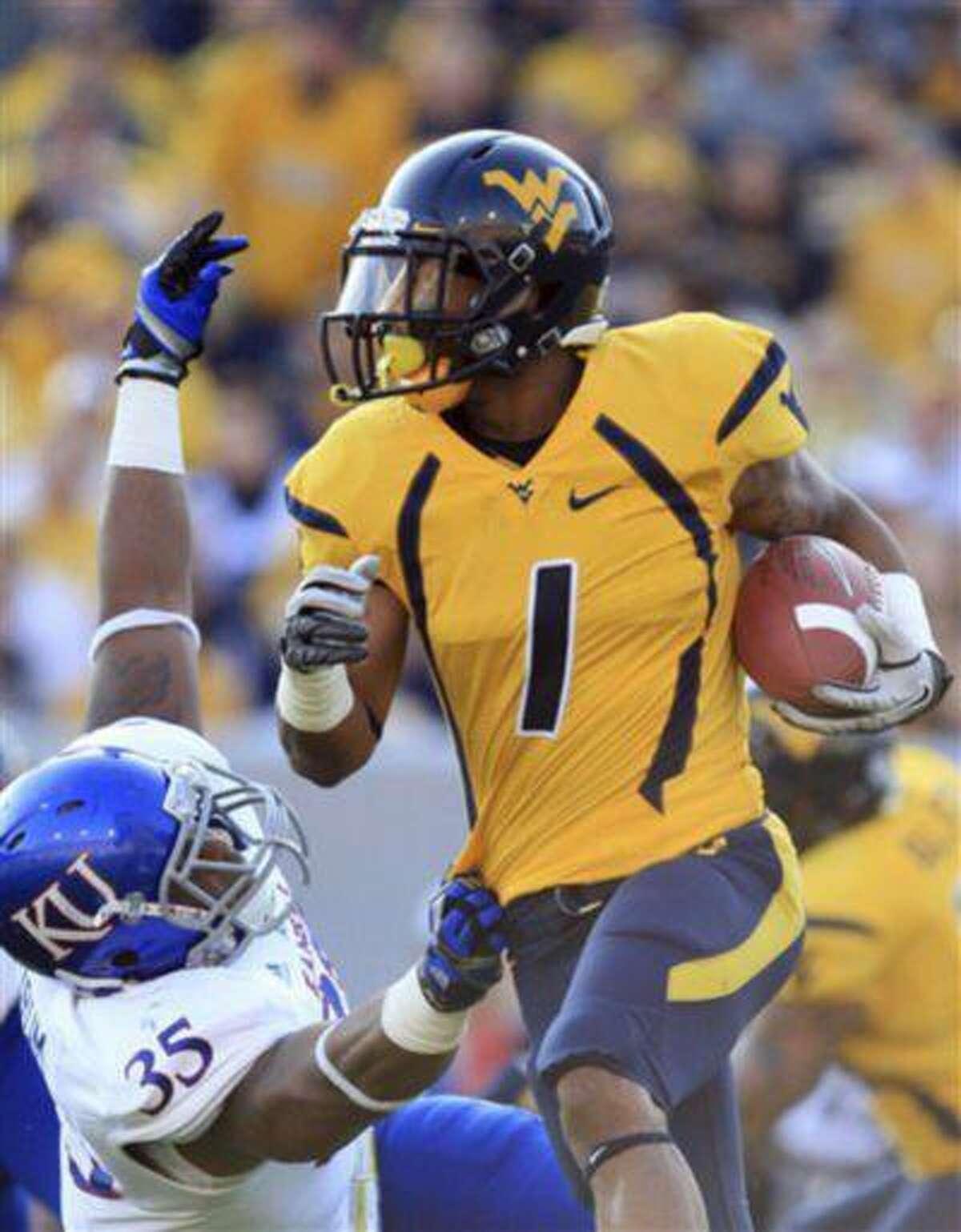 West Virginia's Tavon Austin (1) breaks a tackle by Kansas' Toben Opurum (35) during the first quarter of an NCAA college football game against Kansas in Morgantown, W.Va., Dec. 1, 2012.
