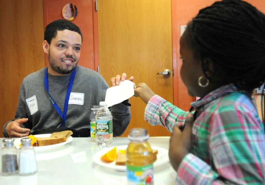 """Jonas Belon, a REACH student at Chapel Haven, left, and  second-grader Jaylese Brown of Edgewood School, participants in the """"Pen and Paint Pal"""" program enjoy a conversation together over lunch Friday, April 26, 2013 at Chapel Haven. Meeting for the first time at Chapel Haven, Chapel Haven students and Edgewood School second-graders  have been participating in a """"Pen and Paint Pal"""" program where they exchange letters and pictures. Photo by Peter Hvizdak / New Haven Register Photo: New Haven Register / ©Peter Hvizdak /  New Haven Register"""