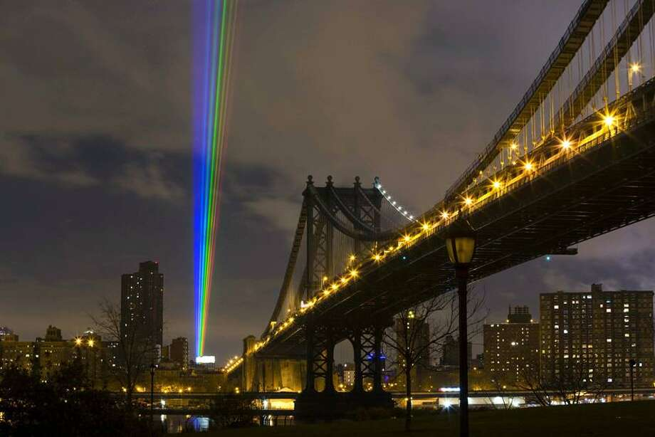 """Photo by James Ewing, courtesy of artist Yvette Mattern + Site Projects: Yvette Mattern laser sculptures have been seen in the night skies around the world, including England, left, and in New York after Superstorm Sandy, """"Global Rainbow: After the Storm,"""" November 2012. / James Ewing Photography"""