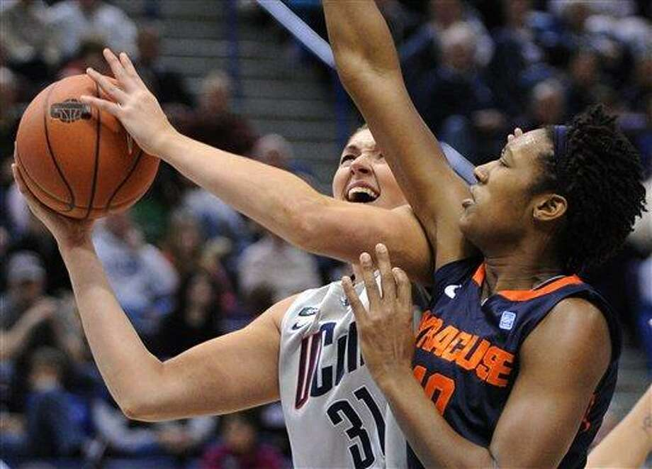 Connecticut's Stefanie Dolson, left, drives to the basket while being guarded by Syracuse's Kayla Alexander during the second half of an NCAA college basketball game in Hartford, Conn., Saturday, Jan. 19, 2013. Dolson scored a game-high 25 points in Connecticut's 87-62 victory. (AP Photo/Fred Beckham) Photo: AP / FR153656 AP
