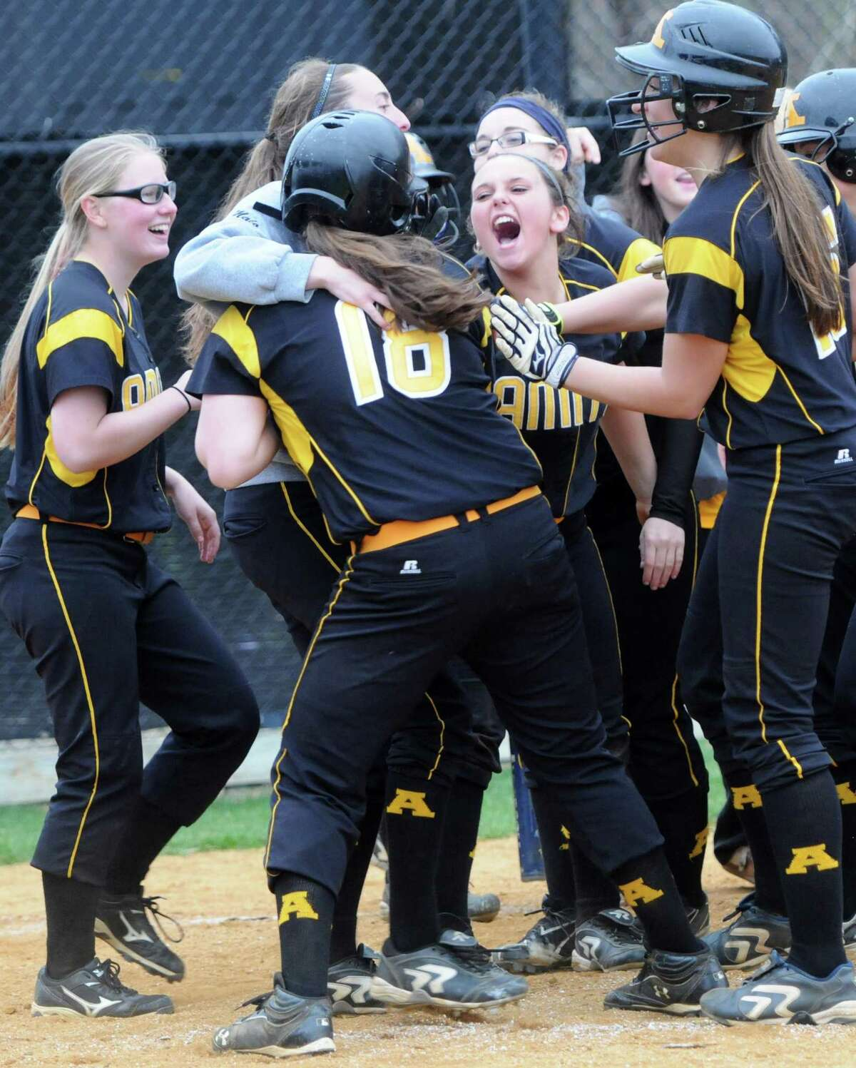 Jenna DiLorenzo of Amity, third from left back to camera, is congratulated by teammates after hitting a home run against Sheehan during fifth-inning softball action at Amity. Photo by Peter Hvizdak /New Haven Register