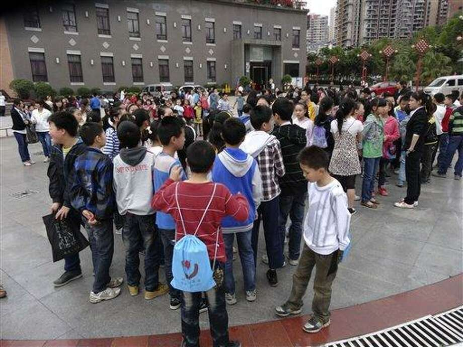 In this photo provided by China's official Xinhua News Agency, students gather outside their school buildings to avoid aftershocks of an earhtquake, in Dazhou,  southwest China's Sichuan Province, Saturday, April 20, 2013. People were killed Saturday when a powerful earthquake jolted China's Sichuan province near the same area where a devastating quake struck five years ago, with state media warning the casualty toll could climb sharply. (AP Photo/Xinhua, Deng Liangkui) NO SALES Photo: AP / Xinhua