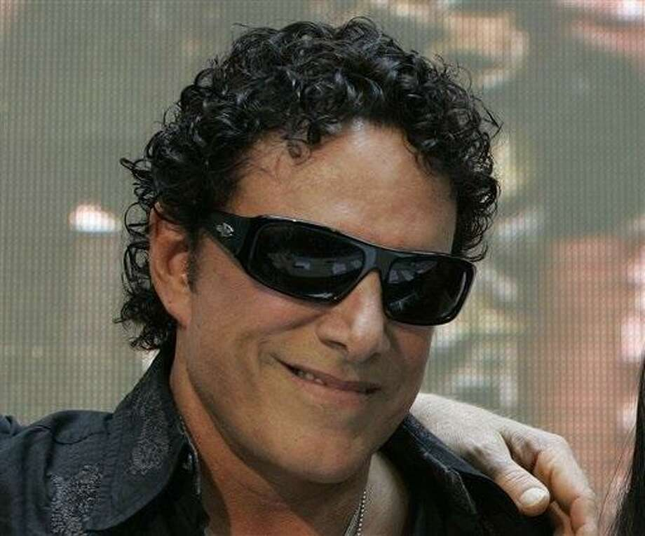 "In this March 2, 2009 file photo, Neal Schon poses for a photograph during a news conference at a mall in suburban Quezon City, north of Manila, Philippines.  Schon, the lead guitarist for the rock band Journey has filed a federal lawsuit in Minneapolis that accuses his former mother-in-law of libeling him in her blog posts. Schon says Judy Kozan, the former mayor of Waseca, has ""attacked and harassed"" him for years through Internet postings and comments in the media. Schon's lawsuit says Kozan suggested that he has failed to support his ex-wife and their two daughters. (AP Photo/Aaron Favila) Photo: AP / AP"