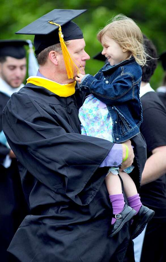 Mike McDonough (left) of Seymour carries his daughter, Saige, 2 1/2, as he waits in line for the Albertus Magnus College Commencement Exercises in New Haven to begin on 5/19/2013.Photo by Arnold Gold/New Haven Register