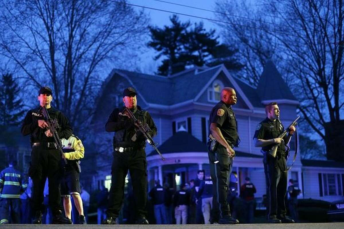Police officers guard the entrance to Franklin street where there is an active crime scene search for the suspect in the Boston Marathon bombings, Friday, April 19, 2013, in Watertown, Mass. Gunfire erupted Friday night amid the manhunt for the surviving suspect in the Boston Marathon bombing, and police in armored vehicles and tactical gear rushed into the Watertown neighborhood in a possible break in the case. (AP Photo/Matt Rourke)