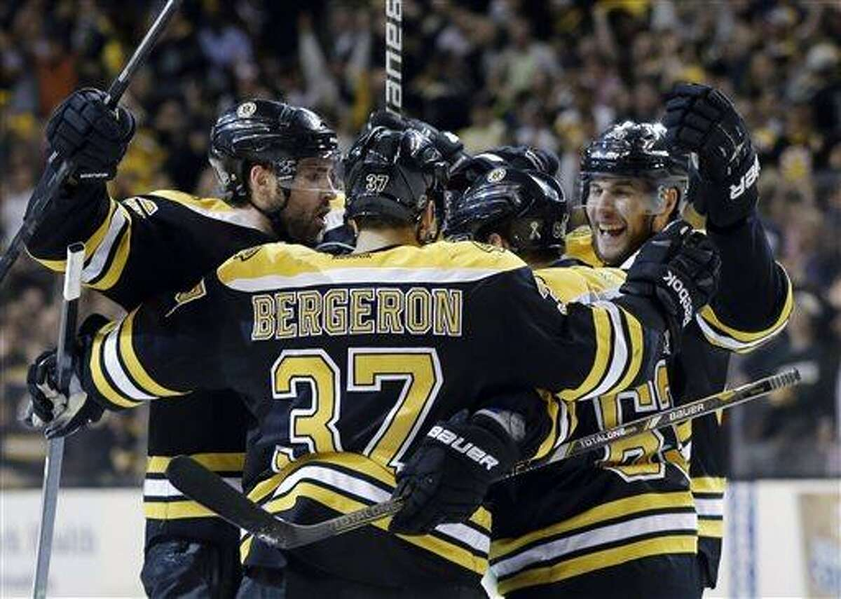Boston Bruins from left, defenseman Johnny Boychuk, center Patrice Bergeron (37), left wing Brad Marchand (63) and defenseman Matt Bartkowski, far right, celebrate a goal against the New York Rangers during the second period in Game 2 of the NHL Eastern Conference semifinal hockey playoff series in Boston, Sunday, May 19, 2013. The Bruins won 5-2. (AP Photo/Elise Amendola)