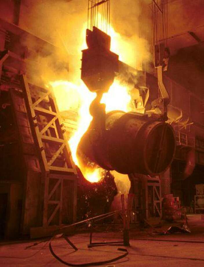 A large caldron of molten steel is poured into a furnace at the Altos Hornos de Mexico (AHMSA) facility in Monclova, Mexico, in this July 1999 photo.