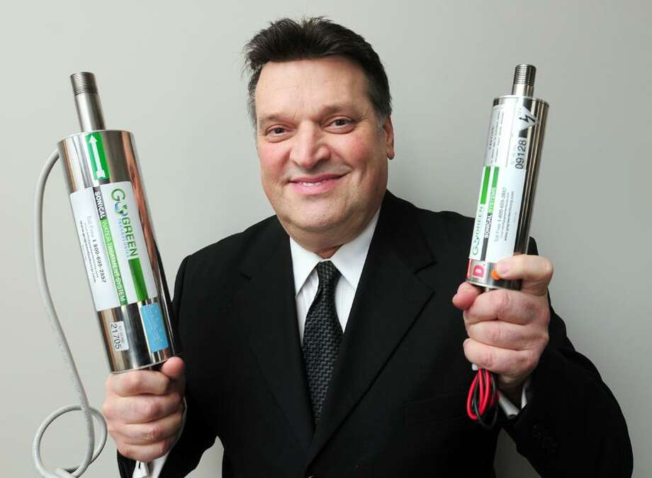 John D'Alessandro, CEO of Go Green Technologies Corp., holds a sonical water treatment system (left) and sonical fuel enhancer system designed for a tractor trailer (right) at his office in Oxford on 2/7/2013.Photo by Arnold Gold/New Haven Register   AG0483A