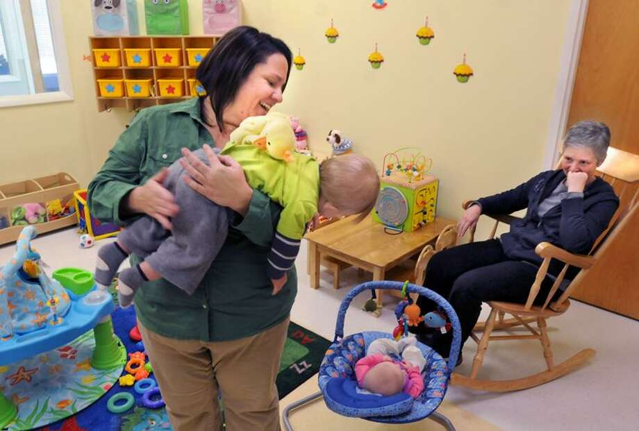 Kelly Barbarotta of North Branford, owner of See Us Grow childcare center in Branford, with Sam Foti, age 11 months of East Haven. Teacher Ana (cq) Boggiatto of Branford kept her eye on a baby.  Mara Lavitt/New Haven Register2/13/13