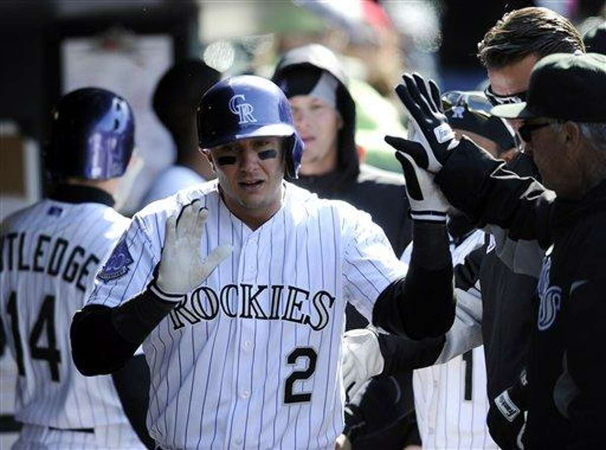 Colorado Rockies' Troy Tulowitzki celebrates a home run with teammates in the dugout during the eighth inning of a baseball game against the New York Mets on Thursday, April 18, 2013, in Denver. (AP Photo/Jack Dempsey)