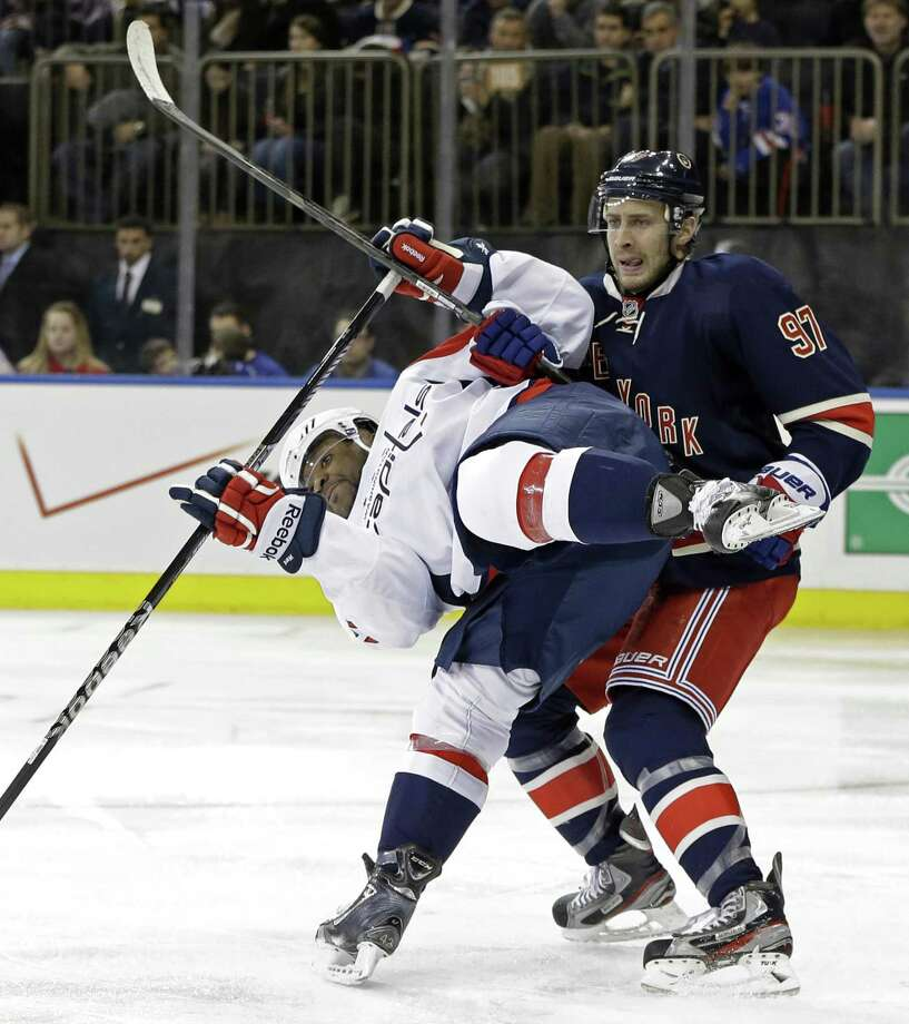 New York Rangers defenseman Matt Gilroy (97) checks Washington Capitals right wing Joel Ward (42) in the third period of their NHL hockey game at Madison Square Garden in New York, Sunday, Feb. 17, 2013. The Rangers won 2-1. (AP Photo/Kathy Willens) Photo: AP / AP