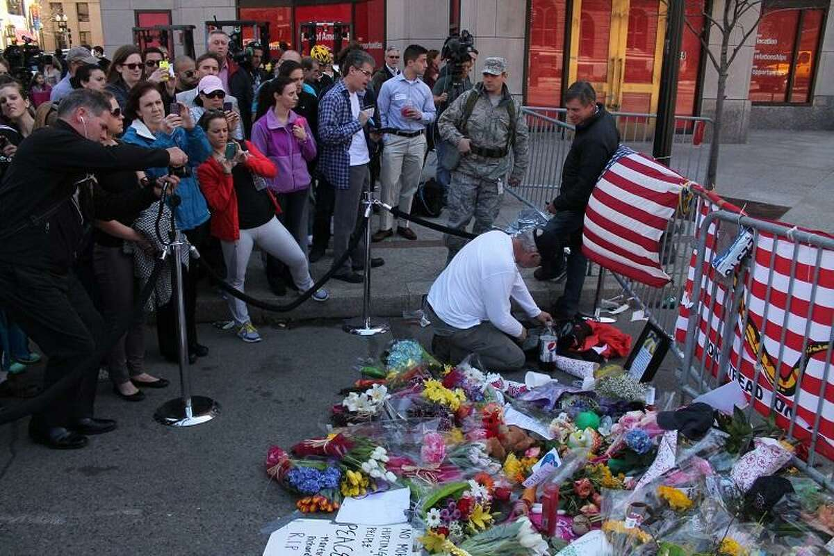 Hyannis resident Ed Starbuck attends to the memorial he created near the bombing sites. Evan Lips/New Haven Register.