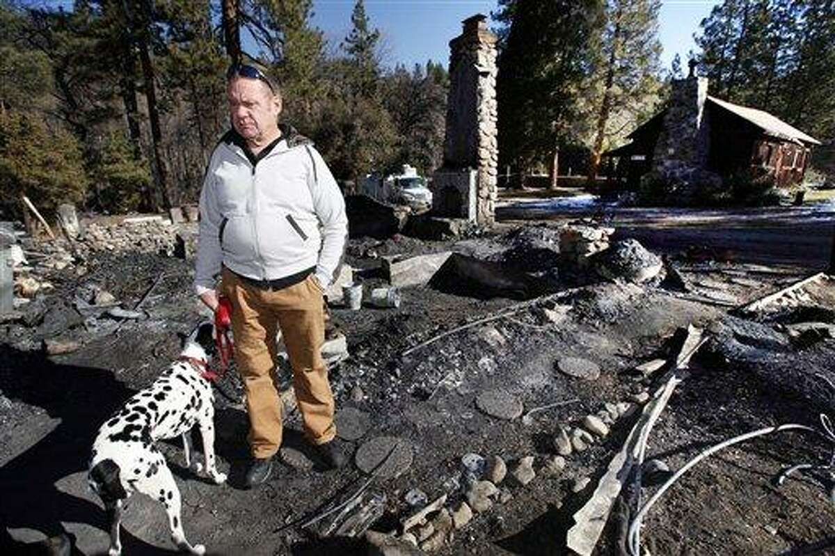 Rick Heltebrake, with his dog Suni, looks over the burned-out cabin where Christopher Dorner's remains were found after a police standoff Tuesday near Big Bear, Calif. Dorner took his pickup during his escape attempt. Heltebrake, a ranger who takes care of a Boy Scout camp, was checking the perimeter of the camp for anything out of the ordinary when he saw Dorner emerge from behind some trees. Photo/Nick Ut