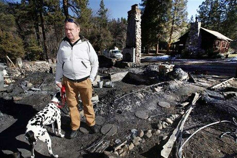 Rick Heltebrake, with his dog Suni, looks over the burned-out cabin where Christopher Dorner's remains were found after a police standoff Tuesday near Big Bear, Calif. Dorner took his pickup during his escape attempt. Heltebrake, a ranger who takes care of a Boy Scout camp, was checking the perimeter of the camp for anything out of the ordinary when he saw Dorner emerge from behind some trees. Photo/Nick Ut Photo: AP / AP
