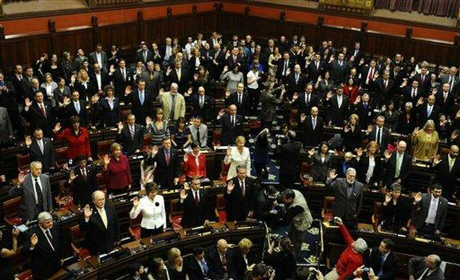 Members of the Connecticut House of Representatives are sworn in at the Capitol in Hartford, Conn., Wednesday, Jan. 9, 2013. Gun control, mental health care and school safety are expected to be major topics in the new session. Legislators also must grapple with a projected deficit of about $1.2 billion. (AP Photo/Jessica Hill) Photo: AP / FR125654 AP
