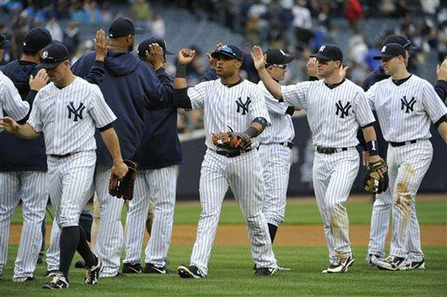 New York Yankees' Brett Gardner, left, Robinson Cano, third from right, Jayson Nix, second from right, and David Adams celebrate the their 7-2 win over the Toronto Blue Jays in a baseball game at Yankee Stadium on Saturday, May 18, 2013 in New York. Cano hit two two-run home runs in the game. (AP Photo/Kathy Kmonicek) Photo: AP / FR170189 AP