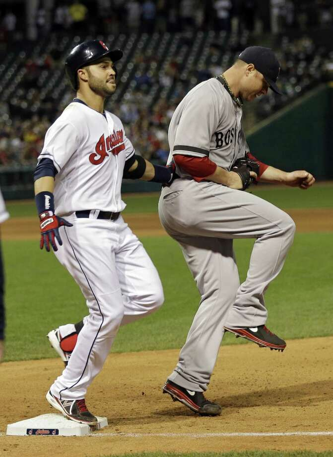 Cleveland Indians' Nick Swisher, left, is out at first with Boston Red Sox starting pitcher Jon Lester covering in the fourth inning of a baseball game Thursday, April 18, 2013, in Cleveland. (AP Photo/Mark Duncan) Photo: ASSOCIATED PRESS / A2012